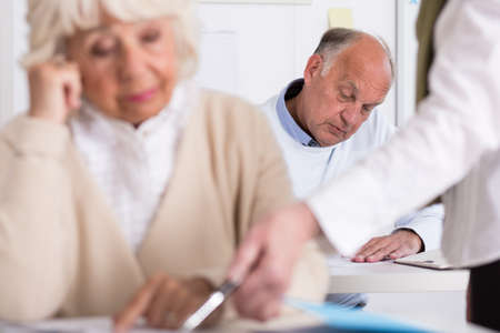 third age: Image of teacher helping senior woman during exam Stock Photo
