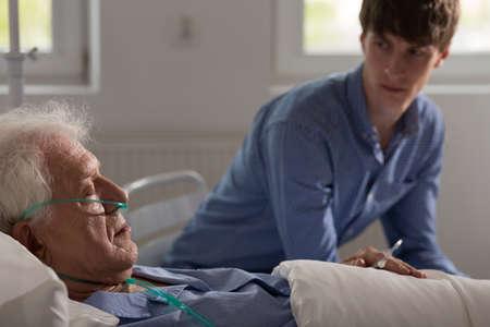 oxygen: Enfermo de más edad con dormir cánula nasal en cama de hospital