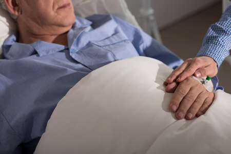 man in hospital bed: Grandson holding his ill grandfathers hand Stock Photo