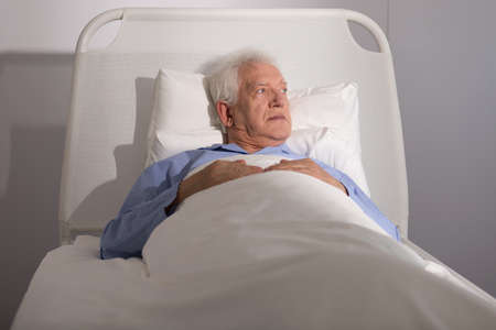 one senior: Elderly sick male patient lying in hospital bed