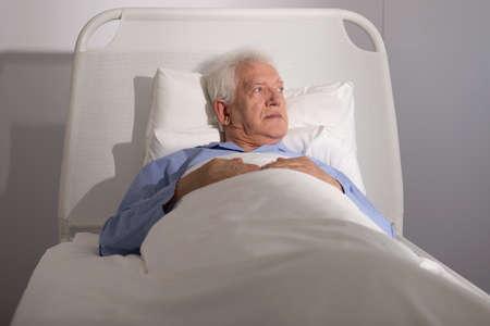 cama: Paciente masculino enfermo mayor acostado en la cama de hospital