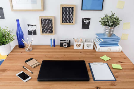 Laptop and mobile phone on wooden office table Standard-Bild
