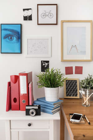 precisely: Binders and books on white nightstand in office Stock Photo