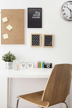 white space: White desk and wooden chair in study room