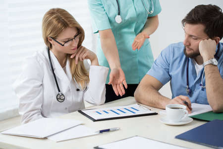 medical doctors: Three doctors in doctors room during medical consultation Stock Photo