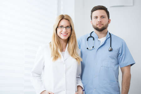 doctors smiling: Two young doctors standing and smiling in a hospital