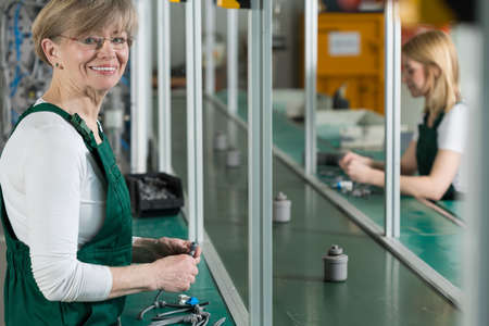 大きな工場で働く高齢者の笑顔の女性
