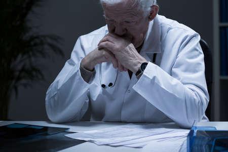 Oude dokter met diepe depressie huilen in eenzaamheid Stockfoto
