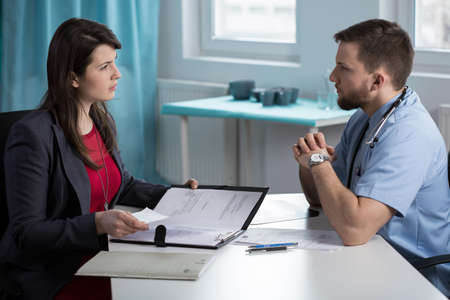 physicians office: Young afraid doctor meeting with lawyer at his office