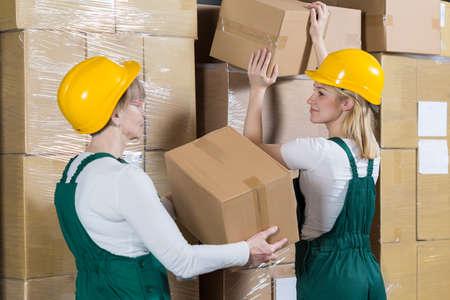 mujer trabajadora: Dos mujeres trabajadores que ponen las cajas en la fábrica
