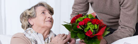 getting together: Senior woman getting bouquet on golden anniversary