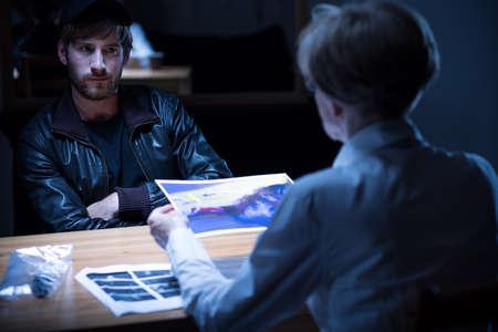 暗い取調室で容疑者の男のインタビュー