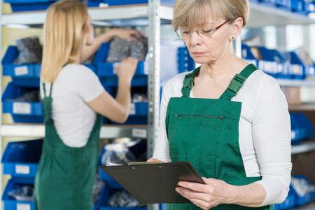 mujeres trabajando: Las mujeres trabajadoras de cheques el almac�n de la f�brica grande