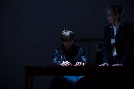 policewoman: Guilty man and elderly policewoman in dark room Stock Photo