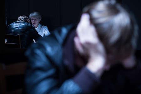testimony: Commissioner interrogating a suspect in dark room Stock Photo