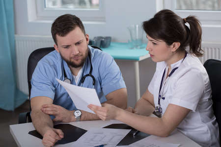 patient's history: Two concerned young physicians looking at patients medical history Stock Photo