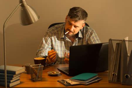 cuarto desordenado: hombre de mediana edad tiene un descanso del trabajo en la oficina Foto de archivo