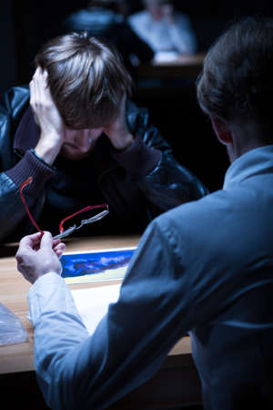 questioned: Man in black jacket questioned in interrogation room Stock Photo
