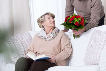 getting together: Man giving his wife bouquet of red roses Stock Photo