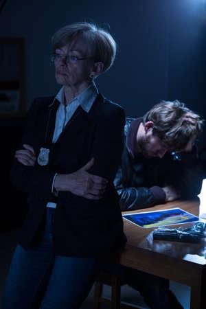 mujer policia: Polic�a pensativo con el hombre sospechoso que mira el cuadro