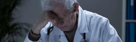 doctor burnout: Melancholic old man with burnout sitting at work