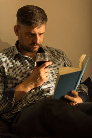 matress: Lonely man with interesting book and good wine Stock Photo