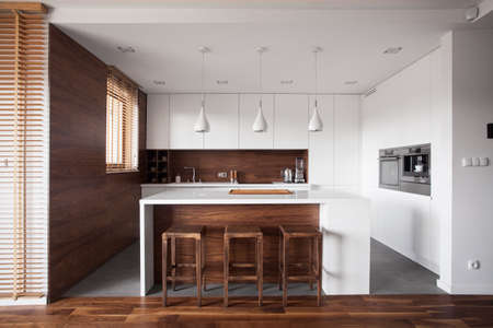 Modern wooden kitchen with white island and dining space