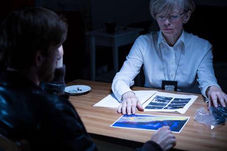 Mujer de la policía que muestra fotos y pruebas del delito a sospechar