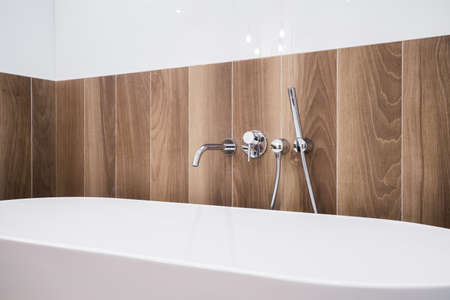 Close-up of white bathtub with wooden panel Reklamní fotografie