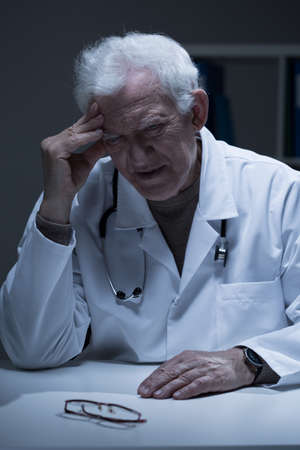 Aged concerned physician sitting alone in office Фото со стока