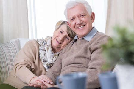 幸せなおばあちゃんとおじいちゃんがソファーに座って