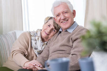 Happy grandma and grandpa sitting on the sofa