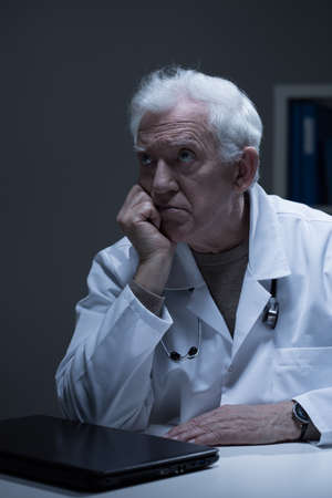doctor burnout: Older bored doctor with burnout sitting in office Stock Photo