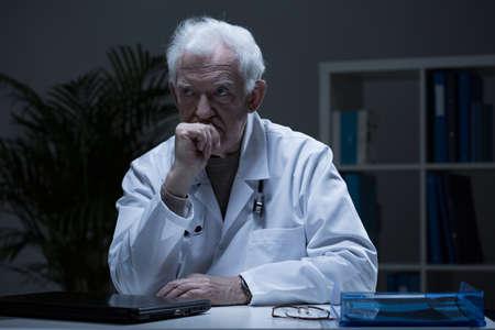 仕事の後、彼のオフィスで一人で座って高齢医師