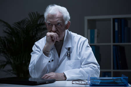 Elderly physician sitting alone in his office after work