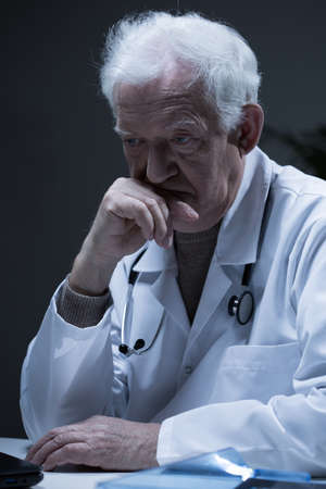 the past: Senior sad physician thinking about his past Stock Photo