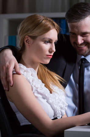 seducing: Young woman and adult manager having romance at work Stock Photo