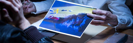 testimony: Close-up of the photo of the crime scene and victim Stock Photo