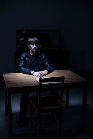 hombre solitario: Sospechoso hombre sentado solo en sala de interrogatorios