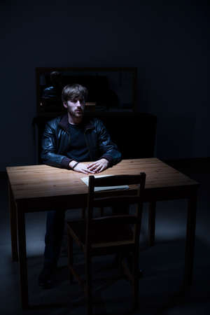 solitude: Suspect man sitting alone in interrogation room