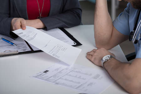 summons: Close-up of lawyer giving the summons to young doctor Stock Photo