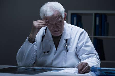 bad color: Elderly worried doctor having bad diagnosis