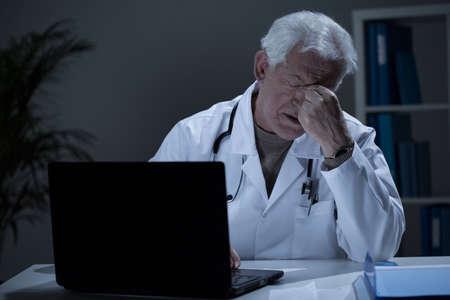 Uitgeput oudere arts met hoofdpijn na dag op het werk Stockfoto