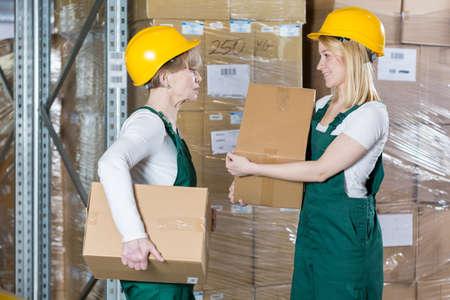mujer trabajadora: Dos fuertes trabajadores de las fábricas sexo femenino que llevan las cajas Foto de archivo