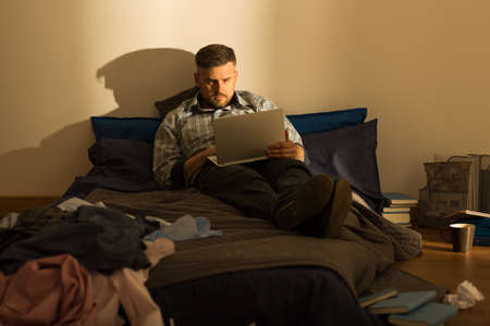 untidiness: Single man is watching something on his laptop