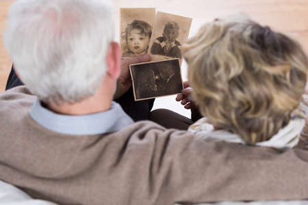 Pares mayores que miran viejas fotos de la infancia