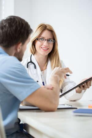 consulta m�dica: Profesionales m�dicos j�venes y felices durante la consulta m�dica