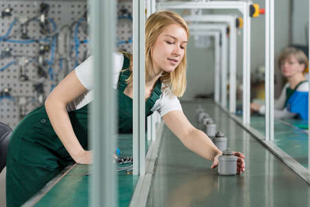 Working young woman reaching for filter part from production line