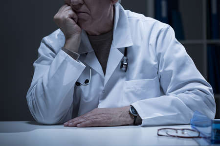 medical cabinet: Close-up of man in medical duster sitting in cabinet
