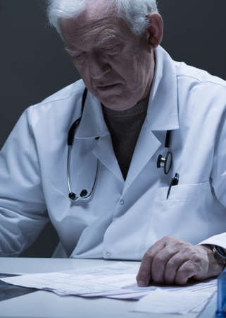 incurable: Older worried doctor checking his test results Stock Photo